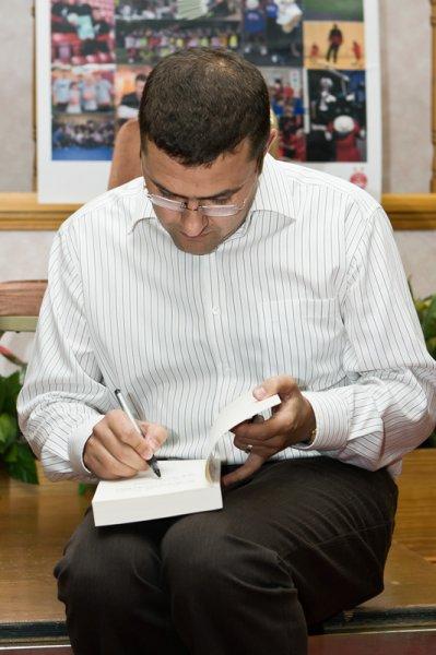 Stuart Donald signs a copy of his book.