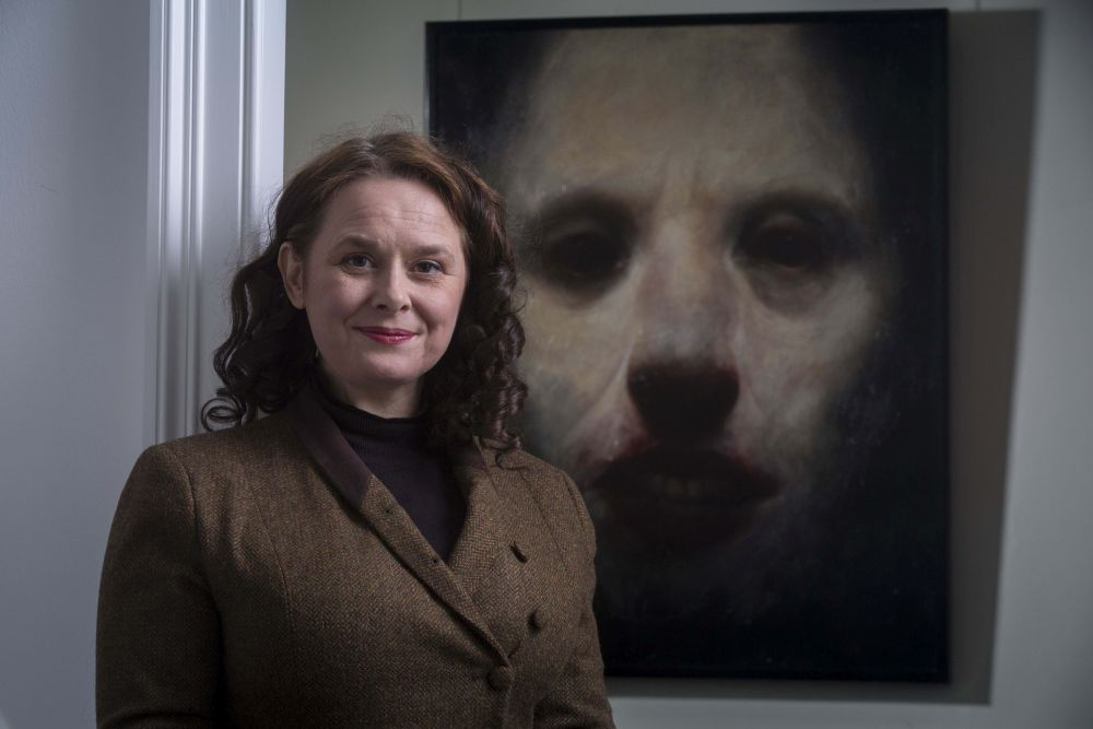 Alison Burke stands before 'Gallowgate Lard' by Ken Currie
