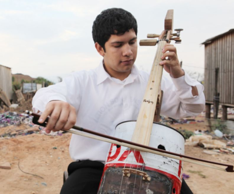 A young musician plays an instrument made from recycled garbage, in Landfill Harmonic.